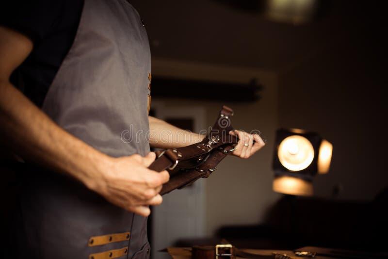 Funktionsduglig process av läderbältet i läderseminariet För fotograf` s för man hållande bälte för kamera Hjälpmedel på trä arkivbild