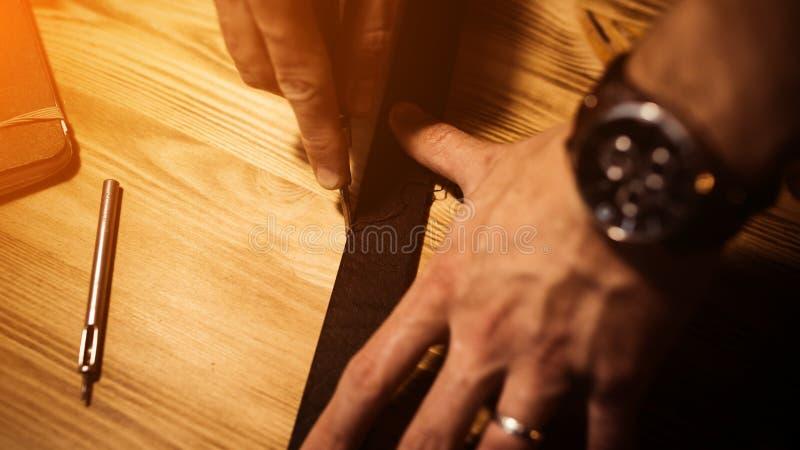 Funktionsduglig process av läderbältet i läderseminariet Hållande hjälpmedel för man Garvare i gammal garveri table trä arkivbild