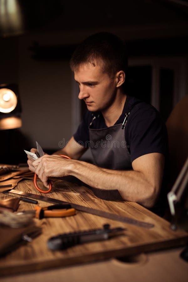 Funktionsduglig process av läderbältet i läderseminariet Maninnehav som tillverkar hjälpmedlet och arbete Garvare i gammalt royaltyfri foto
