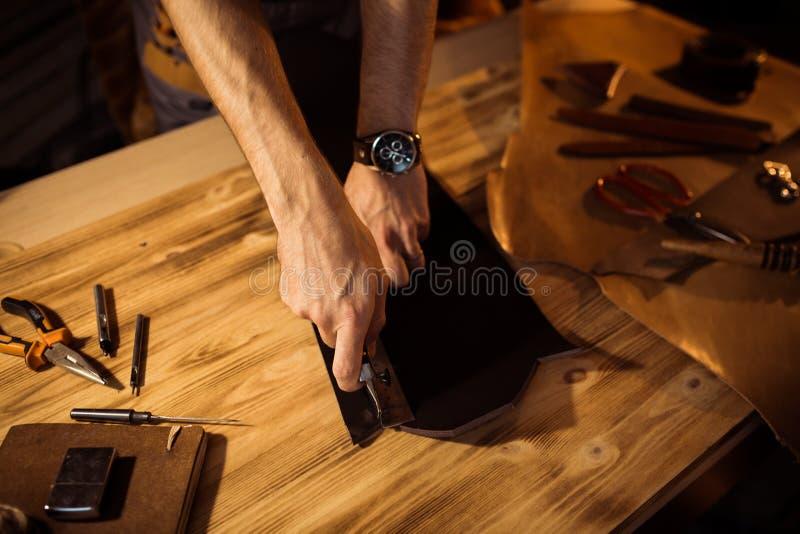 Funktionsduglig process av läderbältet i läderseminariet Maninnehav som tillverkar hjälpmedlet och arbete Garvare i gammalt arkivbilder