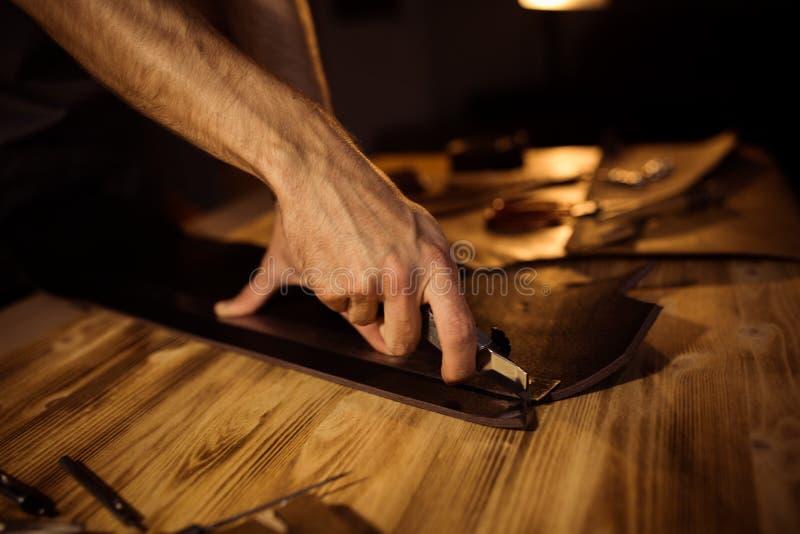 Funktionsduglig process av läderbältet i läderseminariet Maninnehav som tillverkar hjälpmedlet och arbete Garvare i gammalt fotografering för bildbyråer