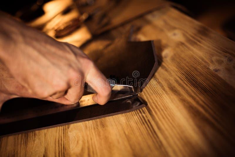 Funktionsduglig process av läderbältet i läderseminariet Maninnehav som tillverkar hjälpmedlet och arbete Garvare i gammalt arkivfoto