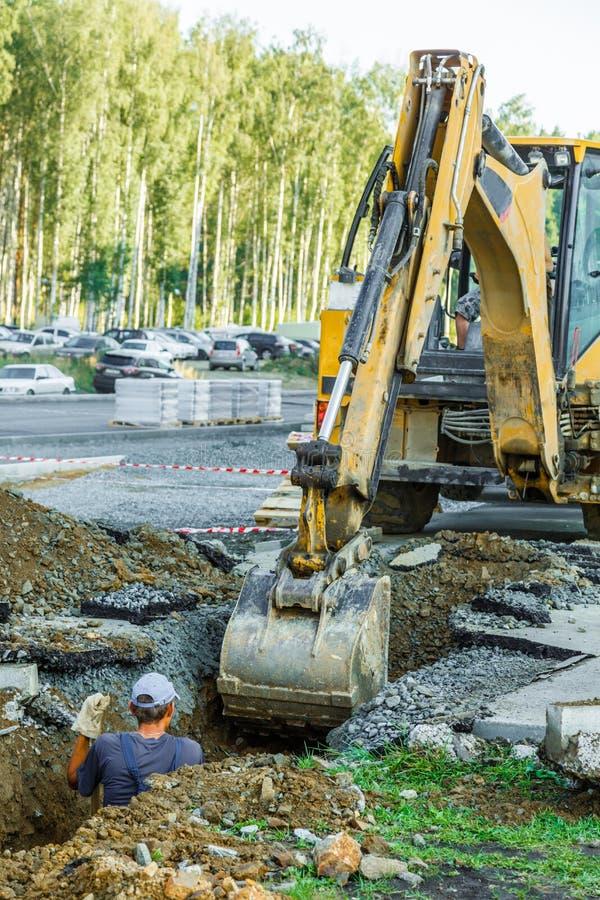 Funktionsduglig yttersida för grävskopa på vägkonstruktion arkivfoto