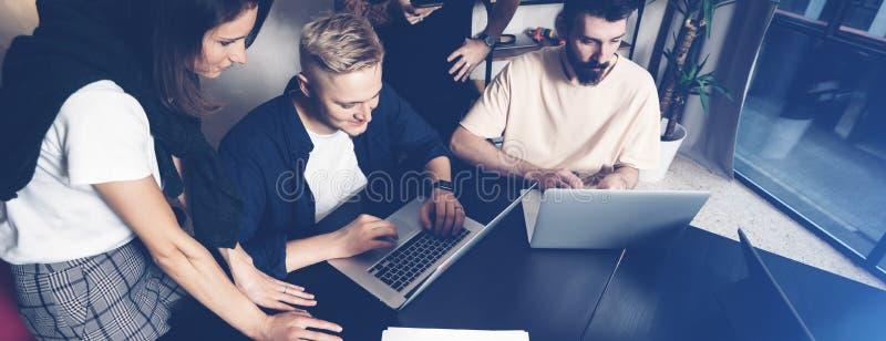 Funktionsdugliga ögonblick Grupp av ungt coworkersfolk i smarta tillfälliga kläder som diskuterar affär, medan arbeta i det idéri royaltyfri foto