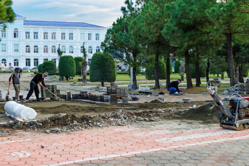 Funktionsdugliga byggmästare lägger den nya förberedande tjock skiva på fot- zon, trottoar bland parkerar i stad arkivbilder