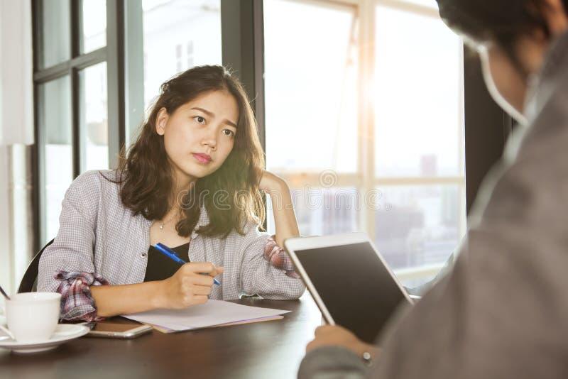 Funktionsdugligt asiatiskt möte för kvinnalag med allvarligt problem på kontor royaltyfri foto
