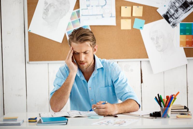 Funktionsdugligt sammanträde för ung stilig säker eftertänksam affärsman på tabellen som tänker över notepaden modern kontorswhit arkivfoton