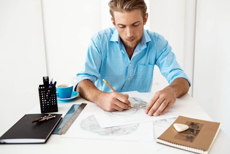 Funktionsdugligt sammanträde för ung stilig säker eftertänksam affärsman på tabellteckningen i notepad Vit modern kontorsinre arkivfoton