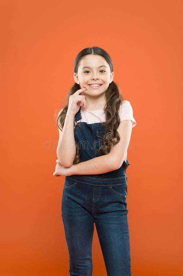 Funky beauty. Adorable baby girl smiling on orange background. Brunette girl with long wavy hair wearing casual style stock photos