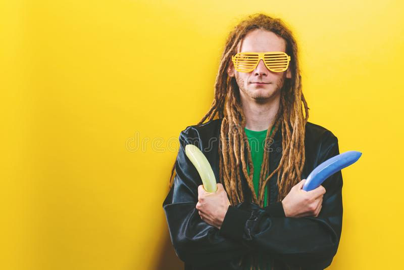 Funky fashion man with dreadlocks. And painted quirky bananas stock image