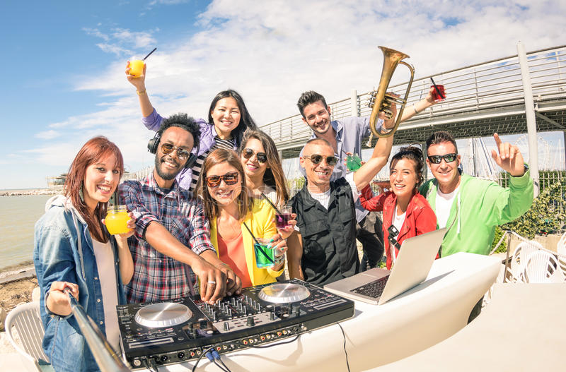 Funky hipster people taking selfie and having fun together at be. Ach rave afterhour party - Summer festival moments with young disc jockey happy friends - Dj royalty free stock photo