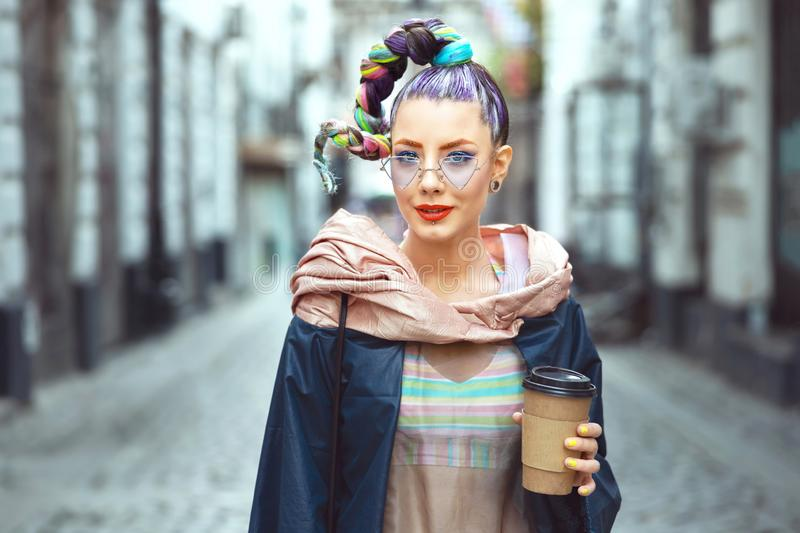 Funky hipster young girl tourist walking city streets holding to go coffee. Cool funky hipster young woman tourist with crazy look and hair wearing trendy avant stock images