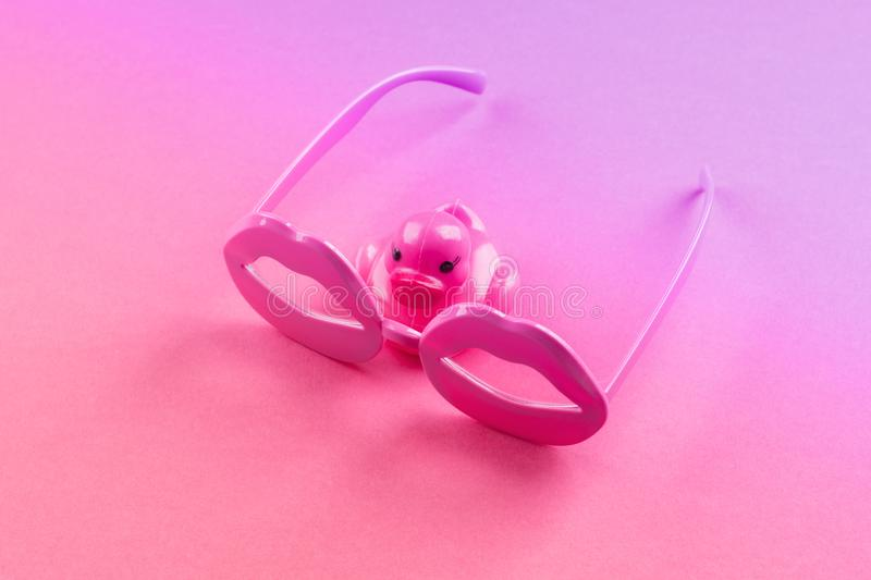 Funky lip shape glasses and rubber duck on pink. Pink funky rubber duck wearing lip shape glasses on neon monochrome. Pop art item composition stock images