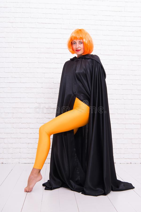 Funky style beauty. Sensual woman in fashion style on white brickwall. Fashion model wearing orange wig hair style and stock image