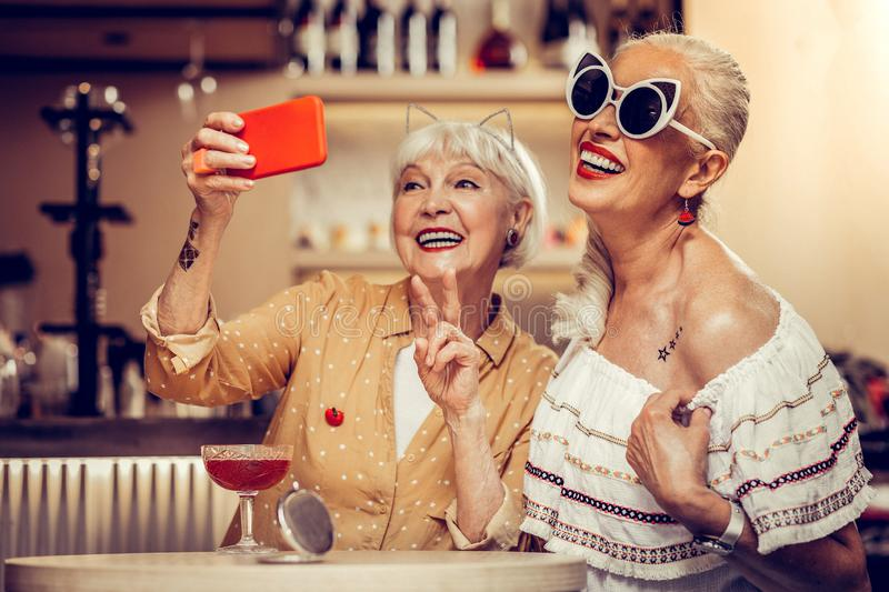 Funky trendy old women making selfie together while visiting bar. Wearing white sunglasses. Funky trendy old women making selfie together while visiting bar and stock photo