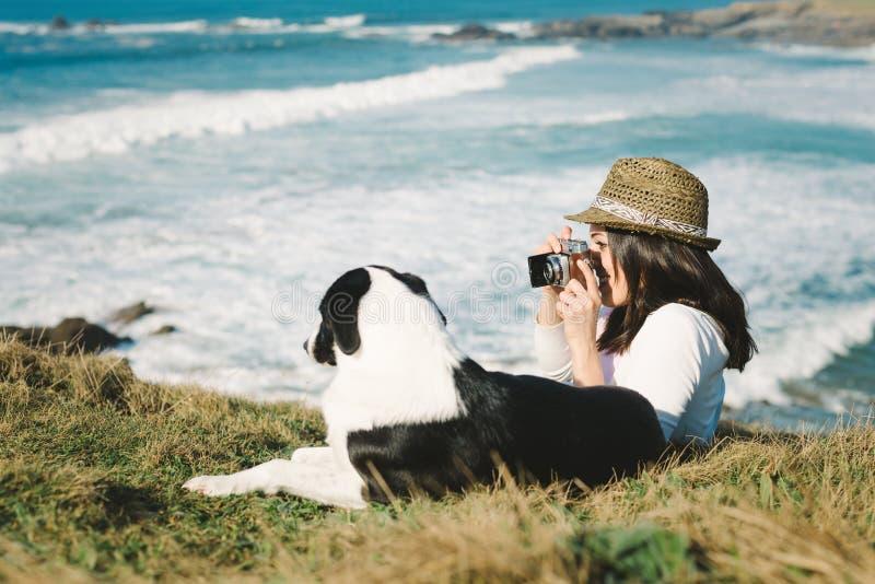 Funky vrouw die foto nemen aan haar hond stock fotografie