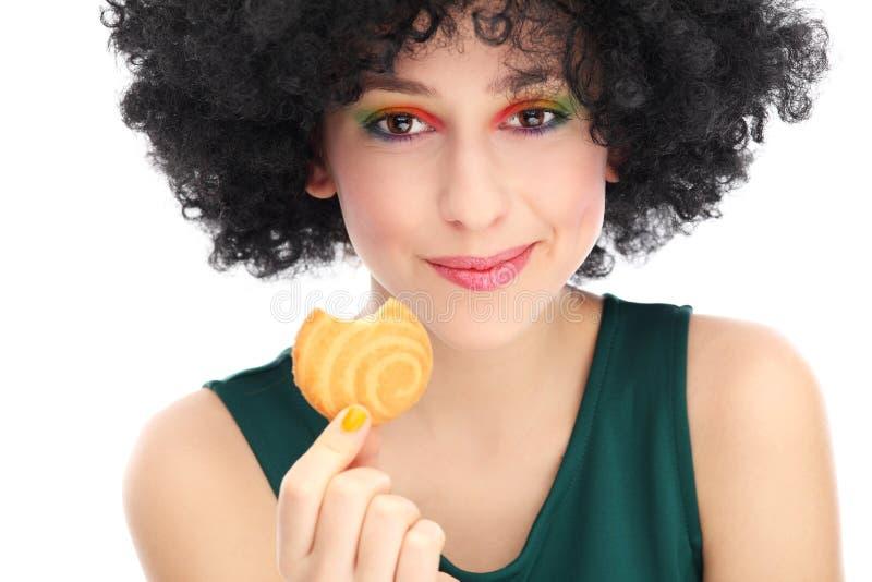 Funky vrouw die koekje eten