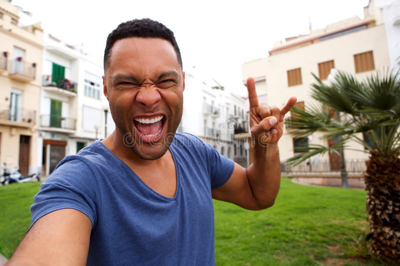 Funky young african man making rock and roll hand sign and taking selfie stock image
