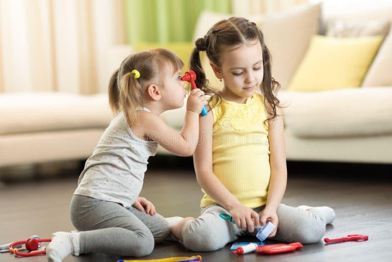 Funna barn spelar läkare med leksaksverktyg Barn som sitter på golvet i vardagsrum royaltyfri bild