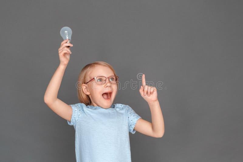funnen lösning Liten flicka i glasögon som isoleras på grått med den ljusa kulan som pekar upp förvånat att le arkivbild