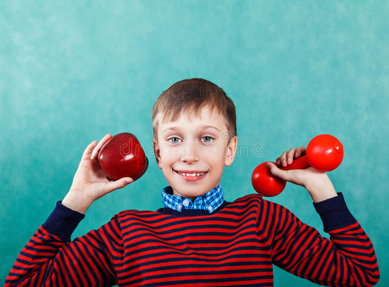 Funny active schoolboy excercising holding an apple and a dumbbell stock photos