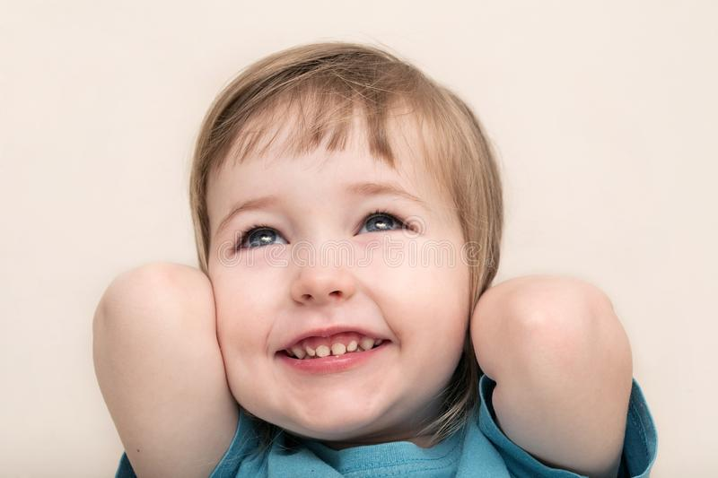 Funny admiration emotional white child girl face closeup. On beige wall background royalty free stock photo