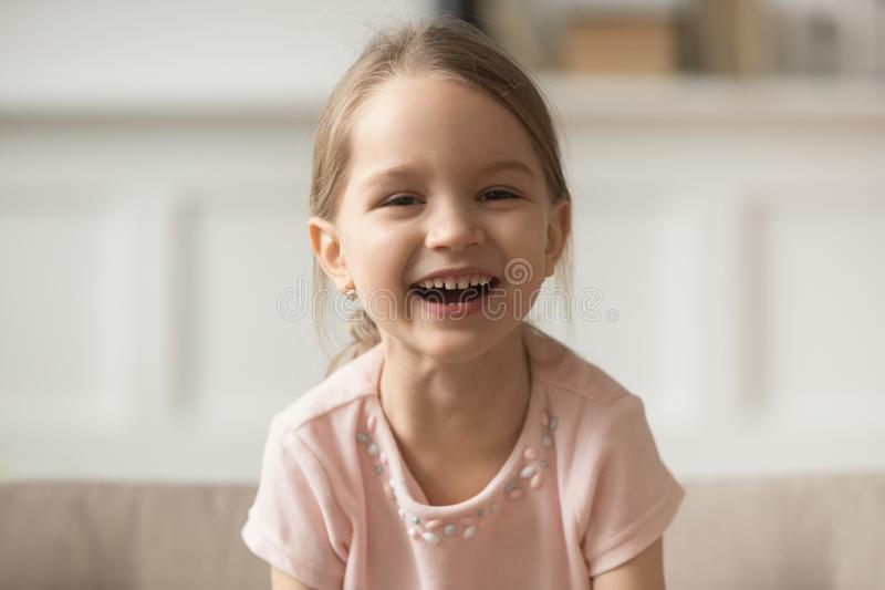 Funny adorable little girl laughing looking at camera, headshot portrait stock images