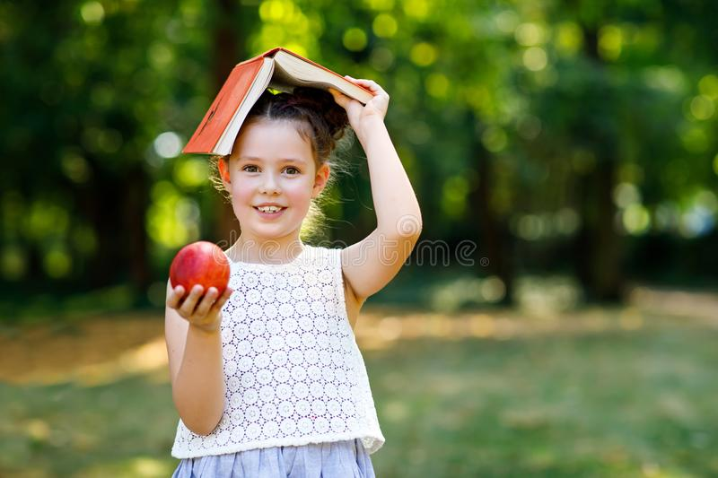 Funny adorable little kid girl with book, apple and backpack on first day to school or nursery. Child outdoors on warm. Sunny day, Back to school concept royalty free stock images