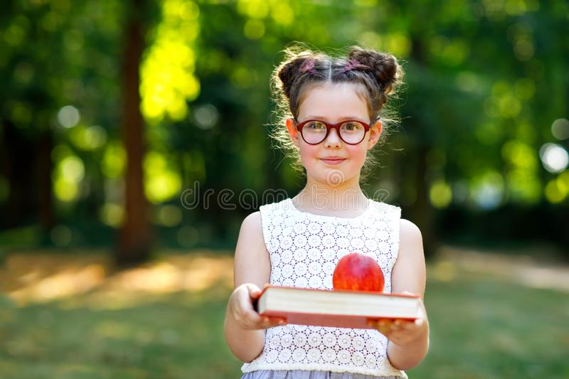 Funny adorable little kid girl with glasses, book, apple and backpack on first day to school or nursery. Child outdoors stock photography