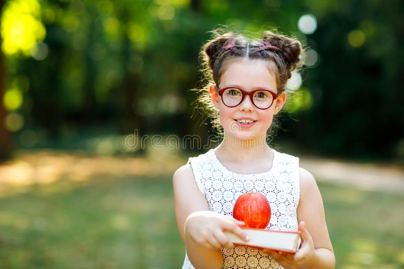 Funny adorable little kid girl with glasses, book, apple and backpack on first day to school or nursery. Child outdoors royalty free stock image