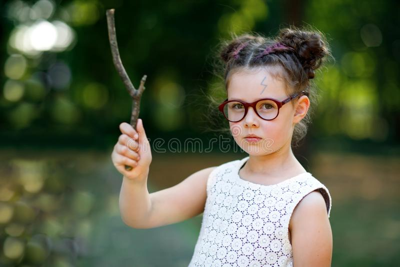 Funny adorable little kid girl with glasses and wooden magic wand playing Harry Potter in park on sunny day. Fan of magic story stock image