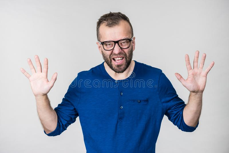 Funny man fooling around. Funny adult man wearing eyeglasses, guy folling around gesturing with hands, trying to be scary. Positive emotions concept royalty free stock photography