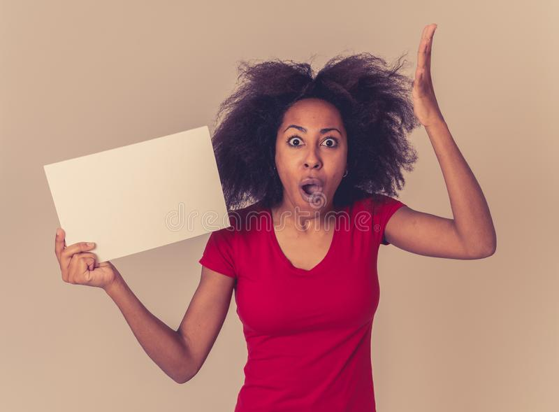 Funny african american woman holding blank board looking surprised and happy pointing at the add royalty free stock photo