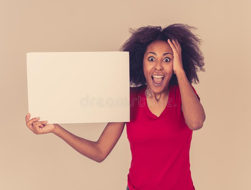 Funny african american woman holding blank board looking surprised and happy pointing at the add royalty free stock image