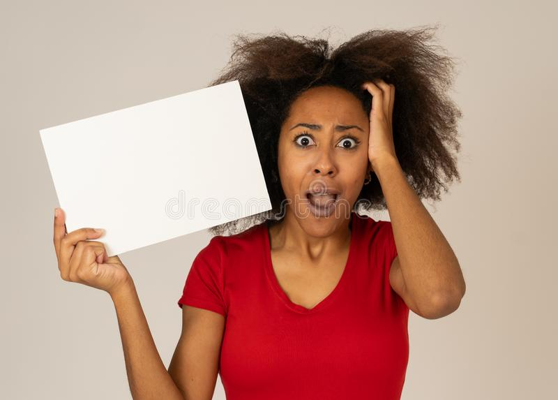 Funny african american woman holding blank board looking surprised and happy pointing at the add stock image