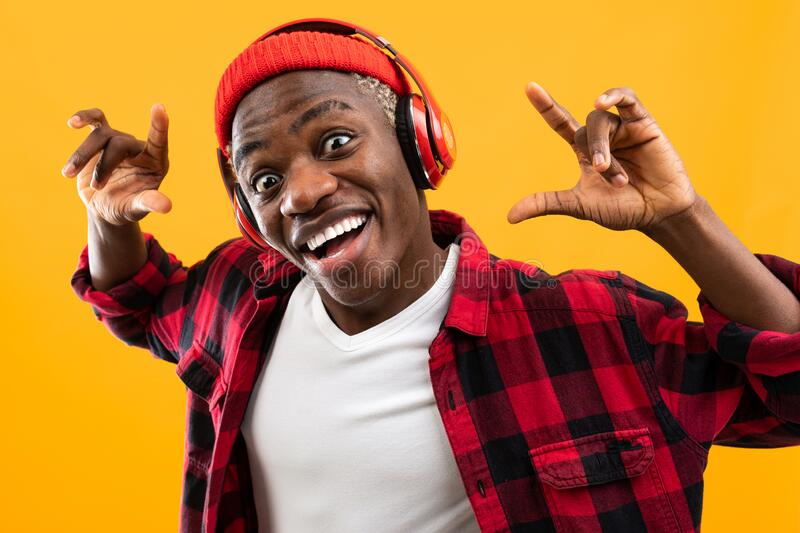 Funny african black man stylishly dressed with a grimace on his face listens to music with headphones on a yellow studio royalty free stock photos
