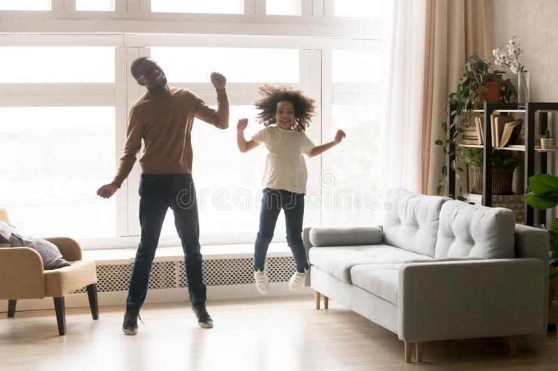 Funny african father and kid daughter laughing jumping at home stock image