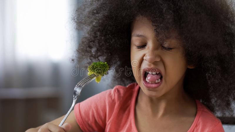 Funny African girl eating broccoli with huge disgust, healthy diet for children royalty free stock image