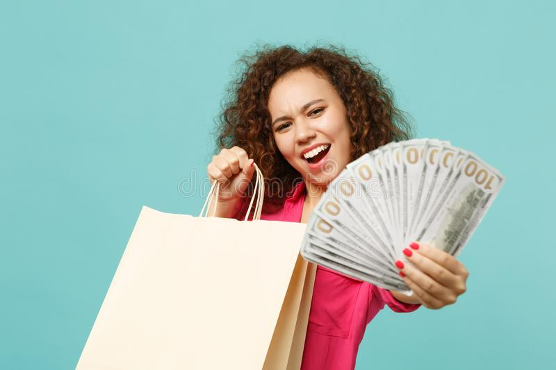 Funny african girl holding package bag with purchases after shopping, fan of money in dollar banknotes, cash money stock photos
