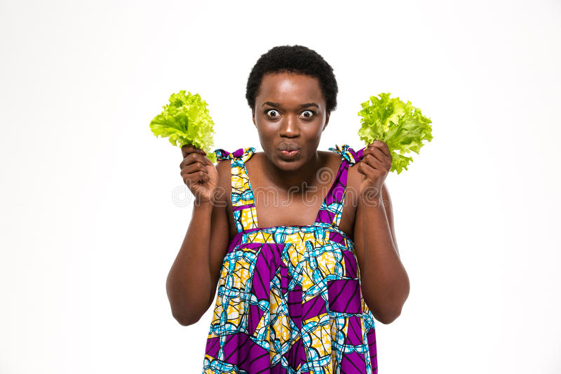 Funny african woman in colorful sundress holding leaves of lettuce stock images