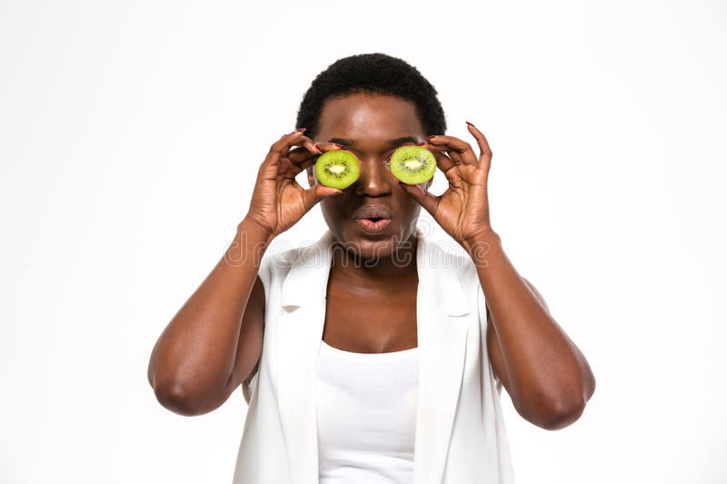 Funny african woman holding kiwi halves in front of eyes royalty free stock photos