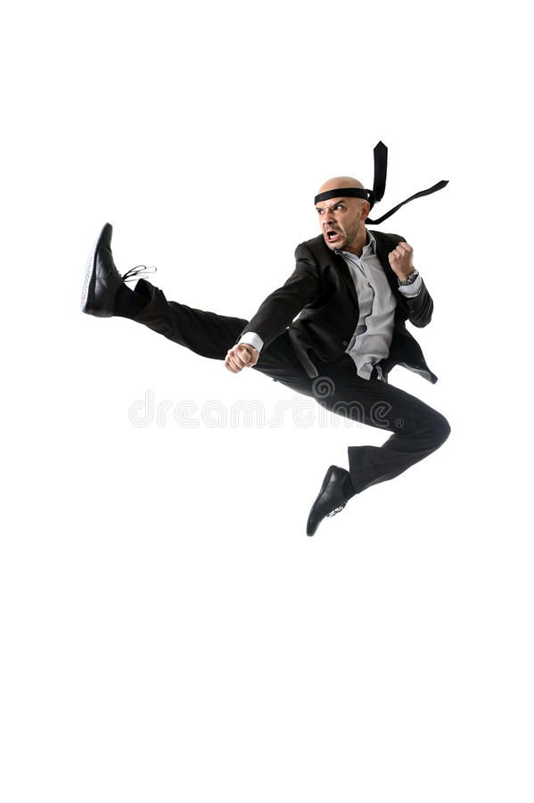 Funny aggressive businessman wearing suit jumping on the air in kung fu kick or karate flying attack royalty free stock photo