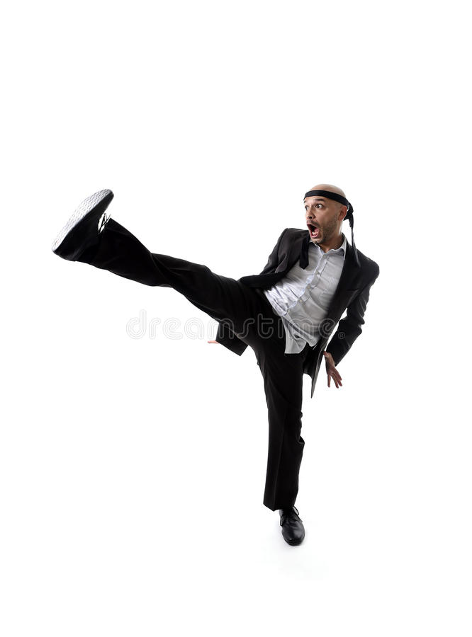 funny aggressive businessman wearing suit in kung fu kick or karate attack royalty free stock images