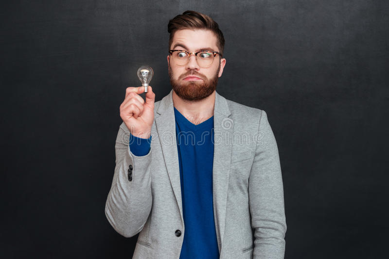 Funny amazed young businessman in glasses holding small light bulb royalty free stock photography