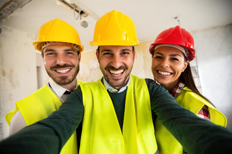 Funny architects workers taking selfie at contruction site. Teamwork stock image
