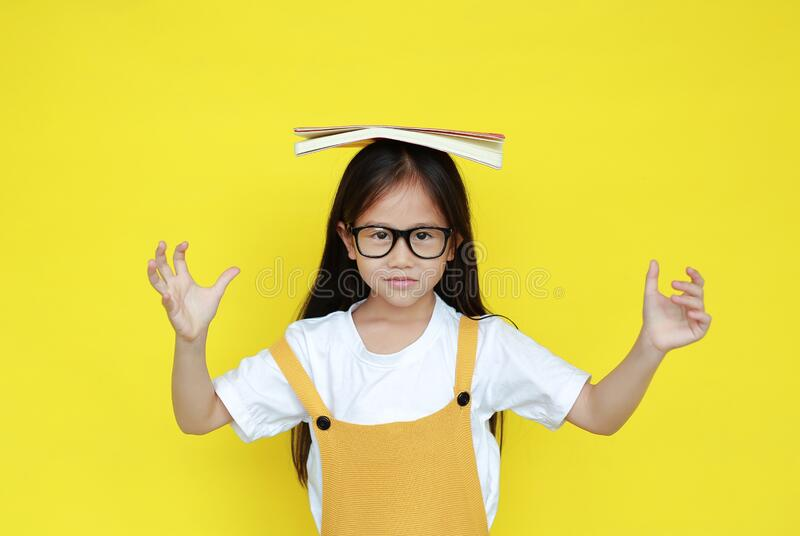 Funny asian little child girl wearing glasses with book on head and looking camera isolated on yellow background. Student and royalty free stock image