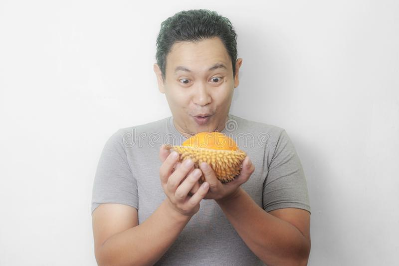 Funny Asian Man Enjoys Durian fruit. Portrait of funny Asian man enjoys yellow durian, king of fruit from Asia, stinky exotic food indonesian malaysian thai lai stock photography