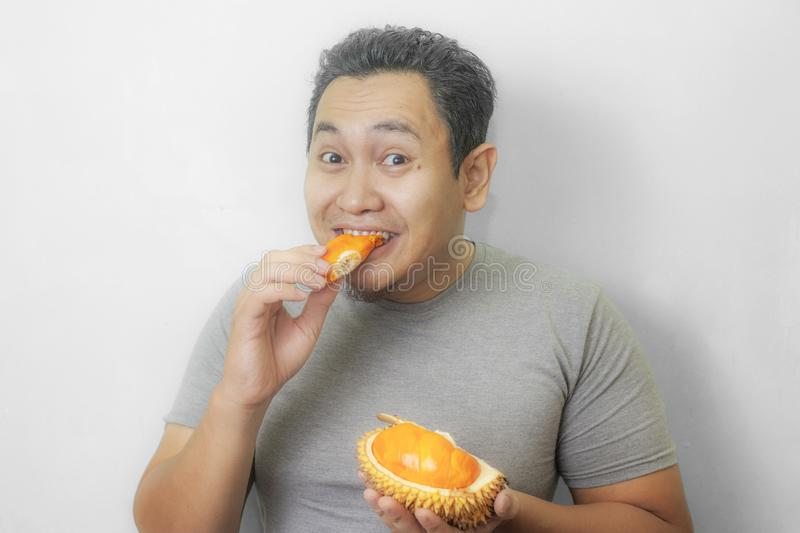 Funny Asian Man Enjoys Durian fruit. Portrait of funny Asian man enjoys yellow durian, king of fruit from Asia, stinky exotic food indonesian malaysian thai lai royalty free stock photography