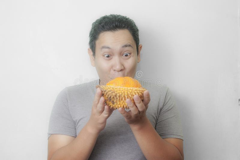 Funny Asian Man Enjoys Durian fruit. Portrait of funny Asian man enjoys yellow durian, king of fruit from Asia, stinky exotic food indonesian malaysian thai lai royalty free stock images