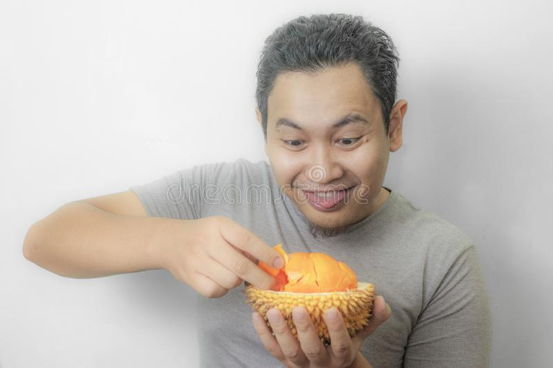 Funny Asian Man Enjoys Durian fruit. Portrait of funny Asian man enjoys yellow durian, king of fruit from Asia, stinky exotic food indonesian malaysian thai lai stock images